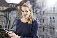Portrait of smiling woman with cell phone on balcony - FMKF03637