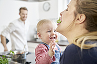 Mother with baby girl in kitchen eating herbs - FMKF03643