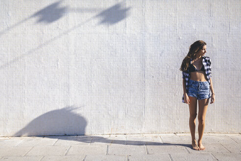 Young pretty woman wearing beach wear standing in front of white wall - GIOF02347