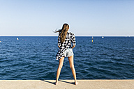 Young woman standing at the sea, rear view - GIOF02359