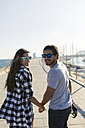 Happy young couple walking at the harbour - GIOF02380