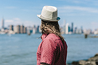 USA, New York City, man wearing hat at the waterfront looking at Manhattan skyline - GIOF02398