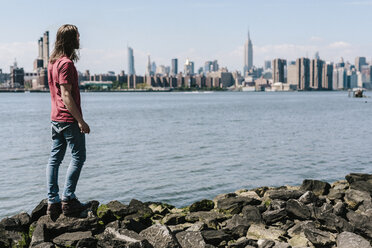 USA, New York City, man standing at the waterfront with Manhattan skyline in background - GIOF02404
