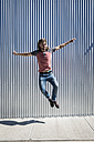 Man jumping mid-air on pavement - GIOF02419