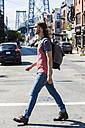 USA, New York City, man crossing the street in Williamsburg, Brooklyn - GIOF02425