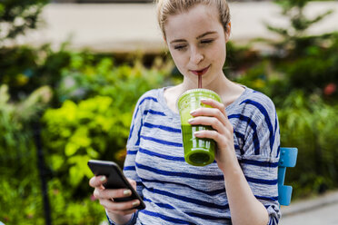 Young woman drinking a smoothie and checking cell phone outdoors - GIOF02448