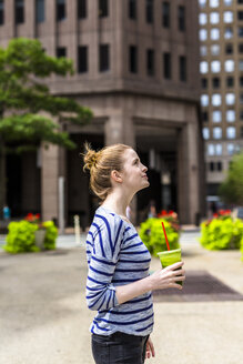 USA, New York City, woman with a smoothie in Manhattan - GIOF02451