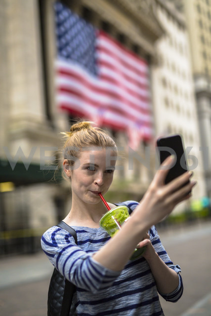 USA, New York City, woman taking selfie in front of New York Stock Exchange - GIOF02463