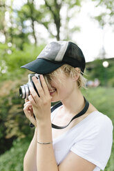 Young woman with a vintage camera taking pictures in park - BOYF00730
