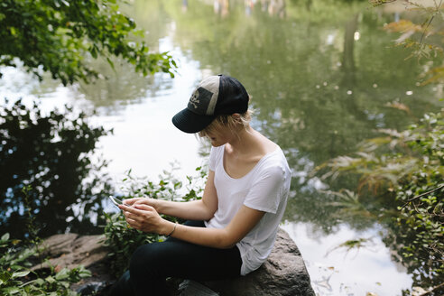 Young woman sitting at lakeside in park looking at cell phone - BOYF00736