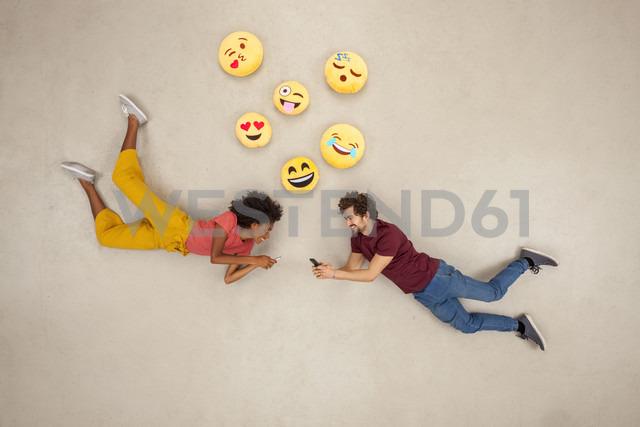 Happy couple texting on their smart phones, sending emojies - BAEF01237