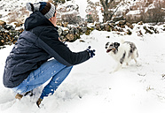 Young man playing with his dog in the snow - MGOF03075