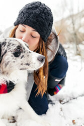 Young woman kissing her dog in the snow - MGOF03078
