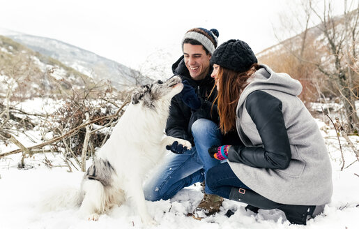Young couple having fun with their dog in the snow - MGOF03081