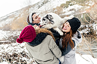 Three friends having fun with a dog in the snow - MGOF03084