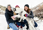 Three friends having fun taking a selfie with a dog in the snow - MGOF03087