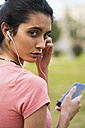 Portrait of female athlete with earphones and cell phone - KKAF00535