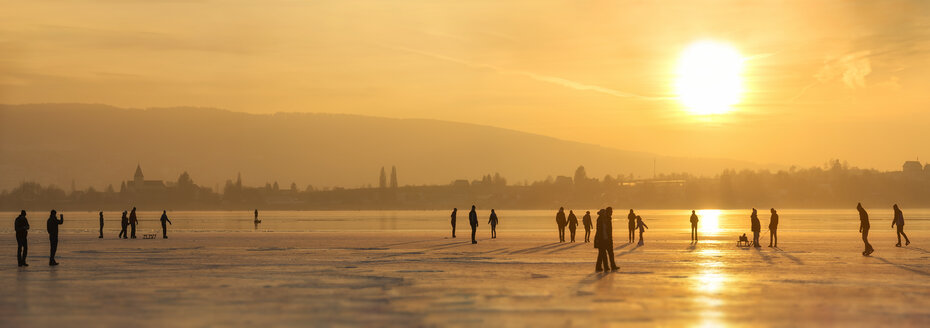 Germany, Lake Constance Hegne, silhouettes of ice skaters and walkers in front of Reichenau at sunset - SHF01950