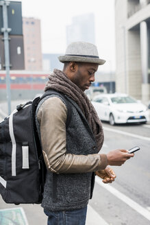 Stylish man with backpack standing beside road looking at cell phone - MAUF00983