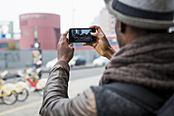 Back view of man taking photo with smartphone - MAUF00989