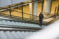 Young man standing on escalator looking around - MAUF00995