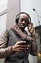 Bald man listening music with headphones looking at cell phone - MAUF01007