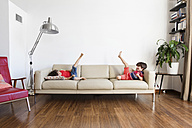 Twin brothers lying on the couch having fun - LITF00536