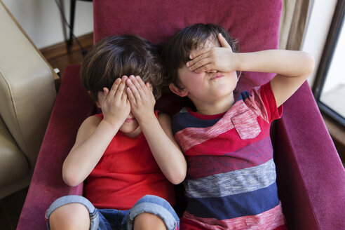 Twin brothers sitting together on arm chair covering eyes with hands - LITF00545