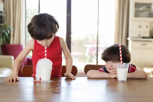 Little boy blowing bubbles in a glass of milk while his brother watching him - LITF00554