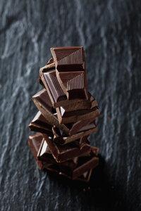 Pile of chocolate pieces on black slate - CSF28121