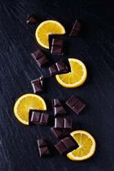 Cocolate pieces with orange slices on black slate - CSF28124