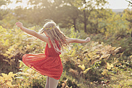 Little girl wearing red summer dress dancing in nature - NMSF00032