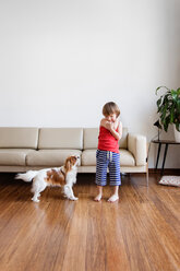 Little boy playing with his dog in the living room - LITF00559