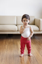 Portrait of daydreaming toddler girl standing barefoot in the living room - LITF00562