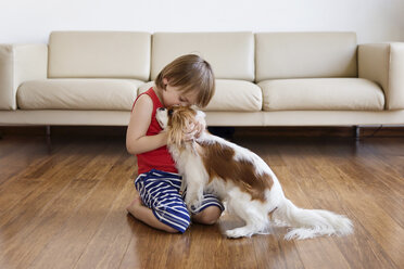 Little boy cuddling his dog in the living room - LITF00568