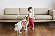 Smiling toddler girl standing in the living room with dog - LITF00571