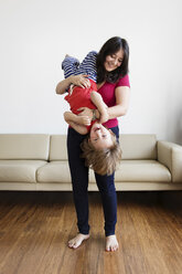 Smiling mother holding her little son upside down in the living room - LITF00574