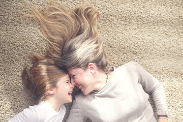 Mother and little daughter lying on carpet having fun - RTBF00752