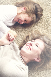 Mother and little daughter lying on carpet having fun - RTBF00755