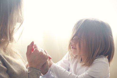 Mother and daughter holding hands at home - RTBF00758