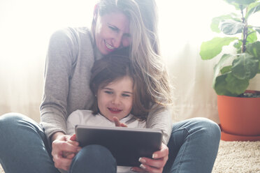 Mother and little daughter using tablet at home - RTBF00761