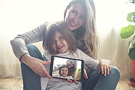 Portrait of mother and little daughter  at home showing tablet with selfie - RTBF00764