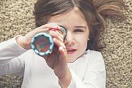 Little girl with kaleidoscope lying on the carpet - RTBF00767