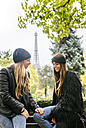 France, Paris, two best friends sitting in a park with the Eiffel Tower in the background - MGOF03092