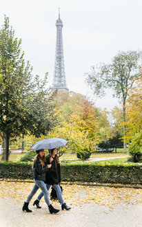 France, Paris, two young women walking in park with the Eiffel Tower in the background - MGOF03095