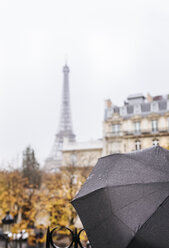 France, Paris, black umbrella with the Eiffel Tower in the background - MGOF03101