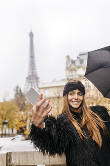 France, Paris, young woman taking a selfie with the Eiffel Tower in the background - MGOF03104