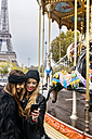 France, Paris, two best friends using their smartphone at a carousel with the Eiffel Tower in the background - MGOF03110
