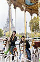 France, Paris, two best friends riding a carousel with the Eiffel Tower in the background - MGOF03113