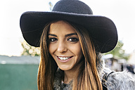 Portrait of smiling young woman wearing a hat - MGOF03119